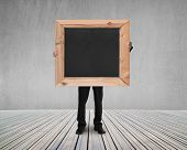 Man Holding Black Blank Chalkboard With Gray Concrete Wall