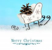 Toy sledge in snow on light blue background