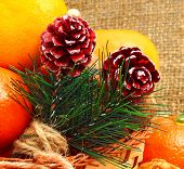 Christmas Pine Twigs With Pine Cones And Tangerines On Christmas Sacking Background