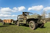 stock photo of army  - Green military army jeep vehicle pulling carriage with wooden boxes filled with bullets to help the soldiers - JPG