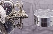 stock photo of reflection  - pocket watch and compass lying on the reflecting surface - JPG