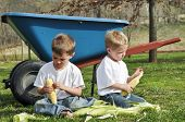 picture of corn  - Two children cleaning corn husks off corn cobs