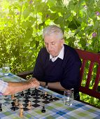 picture of time-piece  - Senior men playing chess in the courtyard - JPG