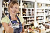 stock photo of local shop  - Sales Assistant In Food Store Handing Credit Card Machine To Customer