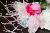 picture of garter  - Beautiful pink rose garter and white stockings lying on a table - JPG