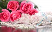 picture of beads  - Beautiful pink roses pearl beads and white stockings with garter lying on a table - JPG