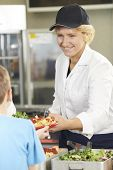 image of school lunch  - Pupil In School Cafeteria Being Served Lunch By Dinner Lady - JPG