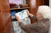 image of wardrobe  - Senior caucasian woman about ninety years old puts towel on the shelf of the wardrobe in her bed room - JPG
