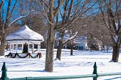 stock photo of gazebo  - village park with snow and gazebo  with Christmas holiday tree and decor - JPG