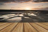 foto of tide  - Beautiful sunrise reflected in low tide water pools on beach landscape with wooden planks floor - JPG
