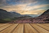 picture of cloud formation  - Stunning sunrise mountain landscape with vibrant colors and beautiful cloud formations with wooden planks floor - JPG