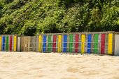 picture of beach hut  - A row of colorful beach huts on the edge of a sandy beach - JPG