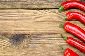 stock photo of chili peppers  - Fresh Red Hot Chili Peppers On The Rustic Wood Kitchen Table - JPG