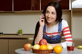 pic of mood  - Brunette housewife wearing in blue denim overalls talking on the phone - JPG