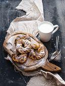 stock photo of cinnamon  - Cinnamon buns with sugar powder on a rustic wooden board mug of milk on dark grunge backdrop - JPG