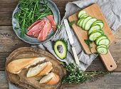 picture of baguette  - Salmon and avocado sandwiches with fresh thyme in baguette tied up with a decoration rope on a rustic wooden board over rough wood background - JPG