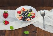 stock photo of porridge  - A bowl of oat porridge with fresh berries honey almond petals and leaves of mint over a piece beige linen fabric on a dark wooden background - JPG