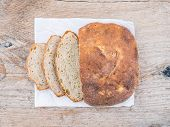 pic of home-made bread  - A half of home made village potato bread over a rough old wood surface - JPG