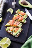 image of avocado  - Sandwich with avocado and smoked salmon on a black wooden board - JPG