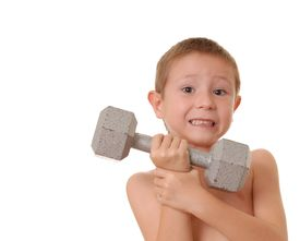 stock photo of lifting weight  - young boy lifting a very heavy dumbbell - JPG