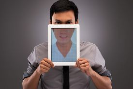 picture of evil  - Portrait of evil man with half of his face covered by digital tablet with an image on happy smile - JPG