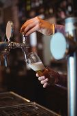 Close-up of bar tender filling beer from bar pump at bar counter poster