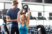Smiling woman using dumbbells with personal trainer in the fitness room. Young woman doing weight ex poster