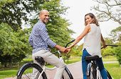 Couple sitting on bicycle while looking behind holding hands. Mature romantic couple riding bicycle  poster