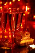 Champagne in glasses and gifts on red background
