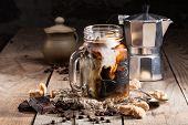 ice coffee in a jar mug with cream and coffee beans, pieces of chocolate, coffee pot on a wooden bac poster