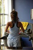Young woman running on the treadmill, fitness series