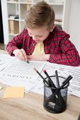 Naughty Young Boy Drawing On Fathers Business Papers At Office poster