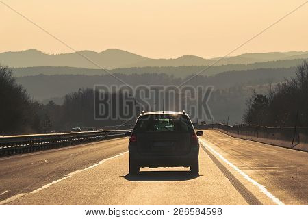 poster of Car Travel In Highway. Traveling By Car On The Road. Car In Highway Landscape In Sunset. Travel By C