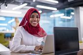 Young modern black muslim business woman wearing a red hijab,working on laptop computer in startup o poster