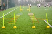Soccer Field With Training Equipment And Fence In Background. Junior Football Team Training With Coa poster