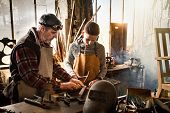 A Craftsman In His Workshop Teaches His Work To His Apprentice poster
