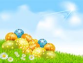 Easter eggs on a green field with daisies and a blue sky