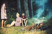 Women And Man At Fire In Camp In Vintage Style. Friends Relax At Campfire. People At Bonfire Flame I poster