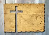 High resolution christian cross cut in an old grungy or vintage paper, over a wood background, ideal