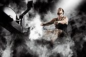 Bearded fit man using rowing machine at functional training gym poster
