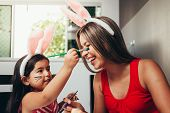 Happy Easter! A Mother And Her Daughter Painting Easter Eggs. Happy Family Preparing For Easter. Cut poster