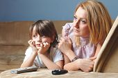 Young mother with her son watch tv, sad and serious face expression