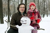 Dad And Daughter Next To The Snowman