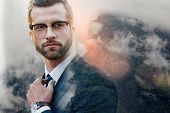 Successful Lawyer. Confident Businessman In Glasses Adjusting His Necktie While Standing Outdoors Wi poster