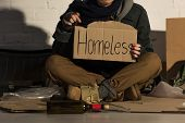 Cropped View Of Homeless Man Holding Piece Of Cardboard With Homeless Handwritten Inscription poster