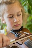 Close Up Of A Child Playing Violin On Green Background. Portrait Of Girl With String And Playing Vio poster