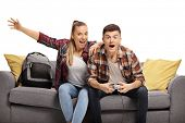 Excited teenage boy and girl sitting on a sofa and playing a video game isolated on white background poster