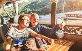 Senior Retired Couple Of Happy Vacationers Taking Selfie At Mekong Exploration Tour With Slowboat In poster