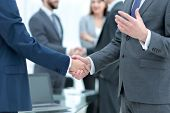 Business partners handshaking over business objects on workplace poster