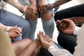 Diverse People Sitting In Circle Holding Hands At Group Therapy poster